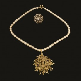 A Mughal pendant set with emeralds, seed pearls and diamonds.