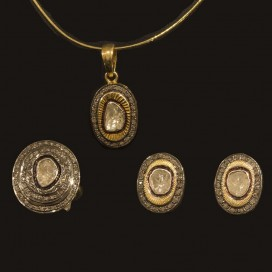 Art Deco set consisting of a pendant, ear tops and ring. All have been set with polki diamonds.